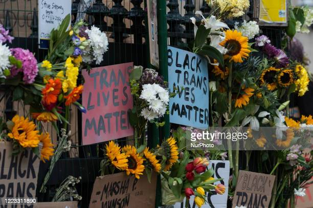 Flowers and placards are left attached to the railings at Westminster tube station after thousands of transgender people and their supporters marched...