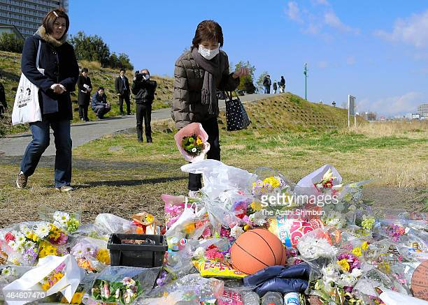 Flowers and prayers are offered at a makeshift memorial where Ryota Uemura's body was found on February 27 2015 in Kawasaki Japan Three teenagers one...