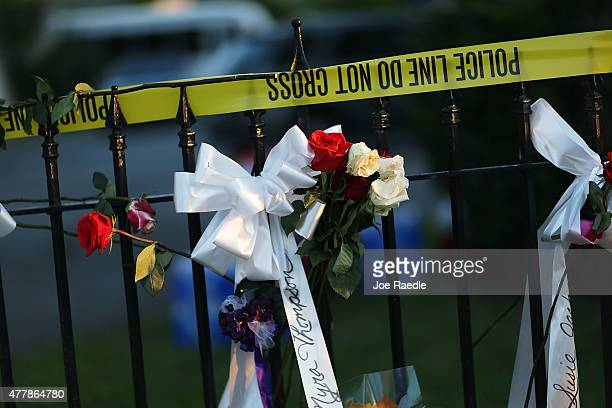 Flowers and ribbons are hung on a fence among the memorial on the sidewalk in front the Emanuel African Methodist Episcopal Church after a mass...