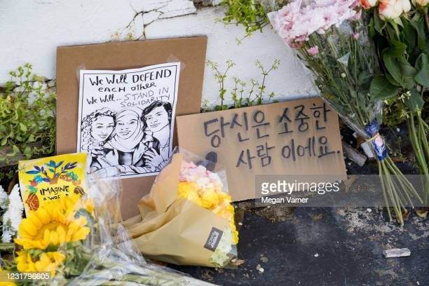 Flowers and signs adorn Gold Spa during a demonstration against violence against women and Asians following Tuesday night's shooting where three...