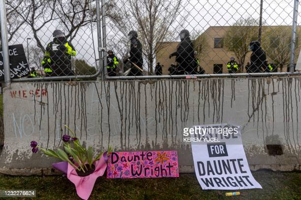Flowers and signs are left in front of the security fence at the start of curfew to protest the death of Daunte Wright who was shot and killed by a...