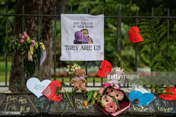 Flowers and tributes are hung on the fence of the Botanic Gardens on March 17 2019 in Christchurch New Zealand 50 people are confirmed dead with 36...