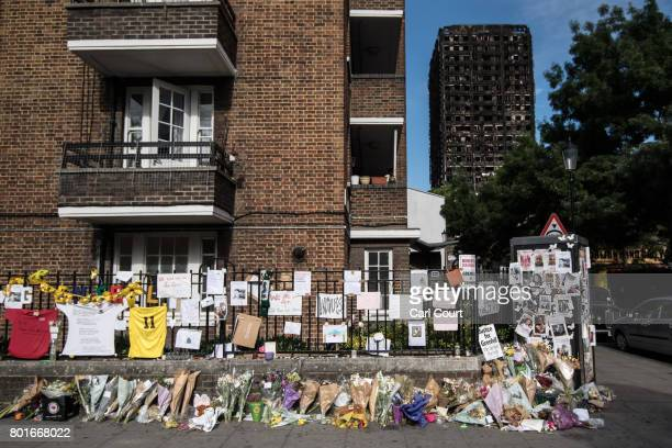 Flowers and tributes are left near Grenfell Tower on June 26 2017 in London England 79 people have been confirmed dead and dozens still missing after...