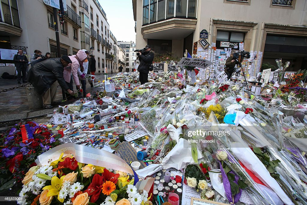 Flowers and tributes are placed on the ground in front of 'Rue Nicolas Appert', close to the 'Charlie Hebdo' offices on January 14, 2015 in Paris, France. An initial three million copies of the controversial magazine were printed in the wake of last week's terrorist attacks. Another two million of the magazine is scheduled for printing.