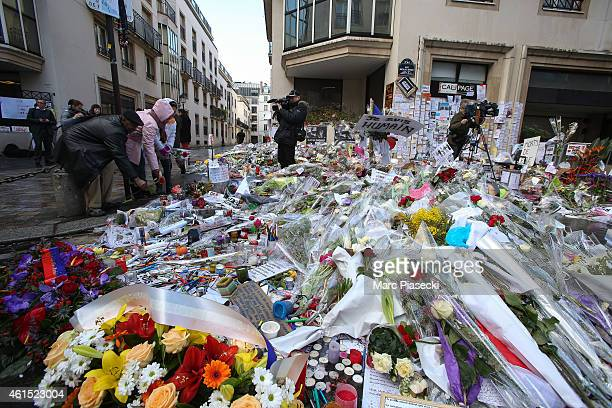 Flowers and tributes are placed on the ground in front of 'Rue Nicolas Appert' close to the 'Charlie Hebdo' offices on January 14 2015 in Paris...