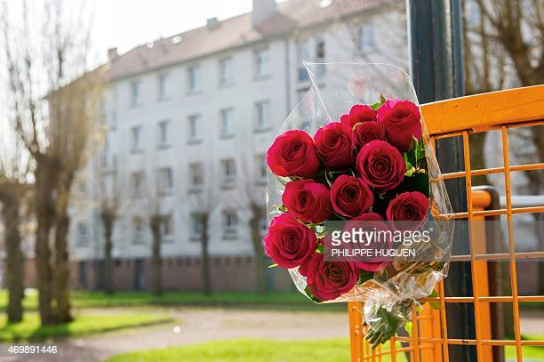 Flowers are attached to a gate on April 16 2015 outside the building where Chloe a nineyearold girl who was snatched on April 15 in front of her...