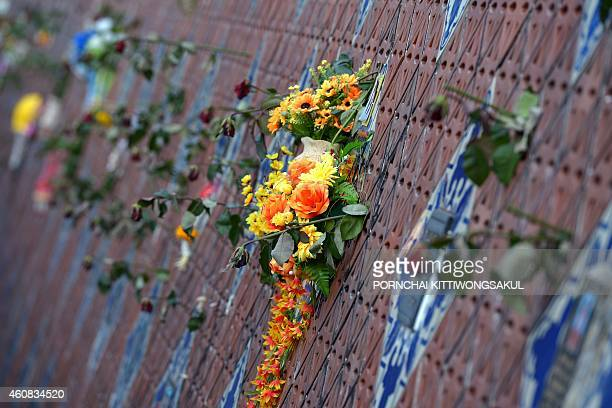 Flowers are displayed on the Ban Nam Khem tsunami memorial park wall on the tenth anniversary of the 2004 tsunami in Phangnga province on December 26...