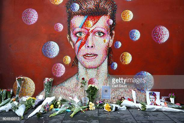 Flowers are laid beneath a mural of David Bowie in Brixton on January 11 2016 in London England British music and fashion icon David Bowie died...