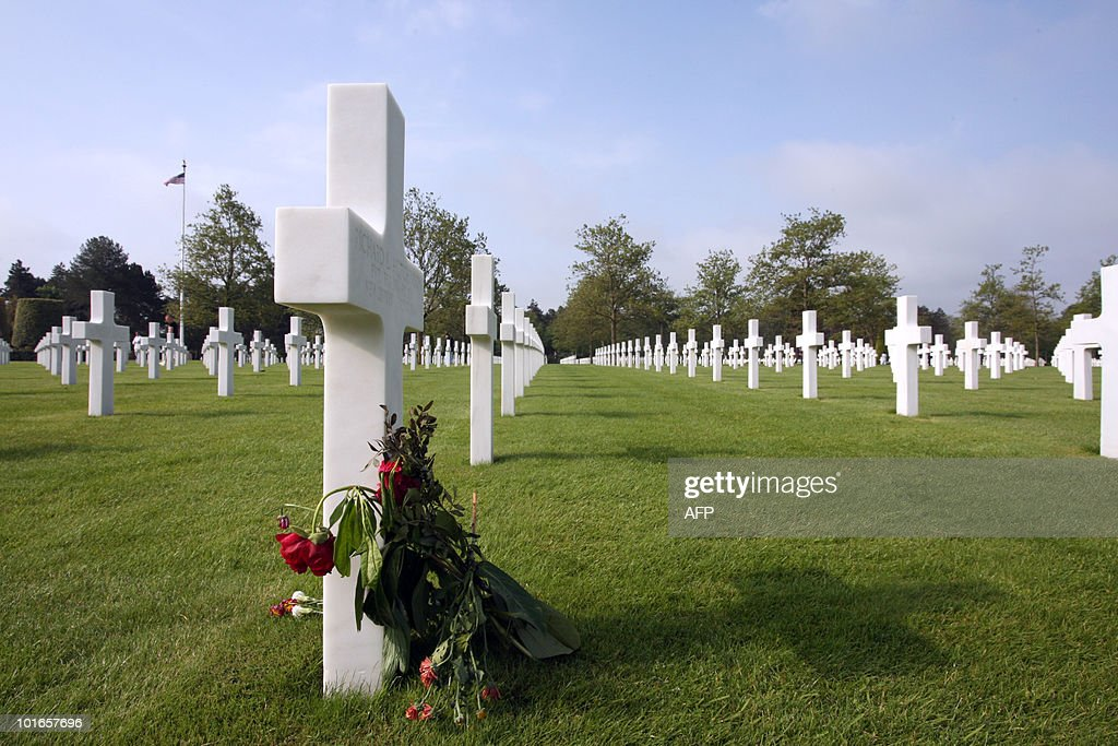 Flowers are laid by a cross at the American cemetery in Colleville-sur-Mer, Normandy, western France, on June 6, 2010, during a commemoration of the 66th anniversary of the D-Day Allied landings on the beaches of Normandy. More than 45,000 Allied soldiers, including 29,000 Americans, were killed during Operation Overlord, which saw the opening of a second front on mainland Europe and led to the liberation of France.