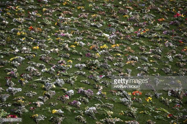 Flowers are laid on the grass by St George's chapel before the funeral service of Britain's Prince Philip, Duke of Edinburgh in Windsor Castle in...