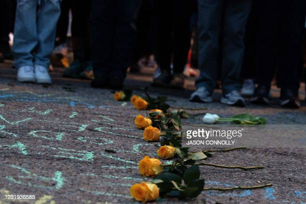 Flowers are laid on the ground representing the 10 people killed in a mass shooting at a King Soopers grocery store in Boulder, Colorado, during a...
