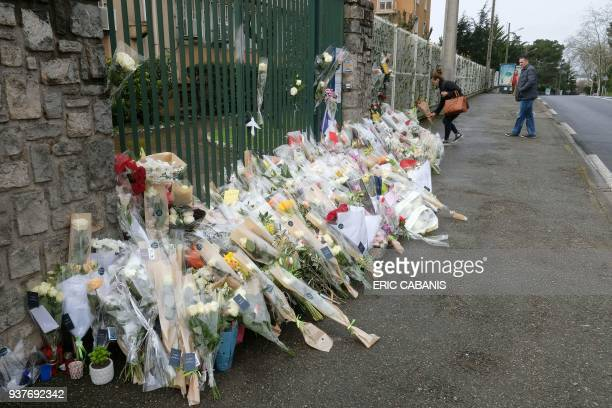 Flowers are laid outside the gendarmerie of Carcassonne where slain LieutenantColonel Arnaud Beltrame worked in southwest France on March 25 two days...