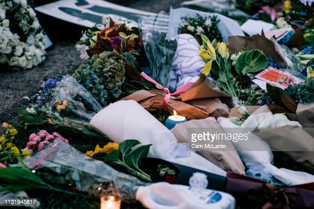 Flowers are left as people attend a vigil for the lives taken in the Christchurch terror attacks at the Auckland Domain on March 22 2019 in Auckland...