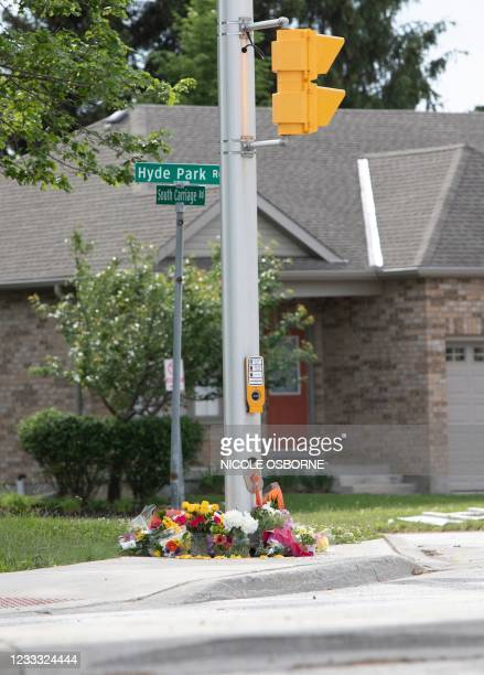 Flowers are left as people pay their respects at the scene where a man driving a pickup truck struck and killed four members of a Muslim family in...