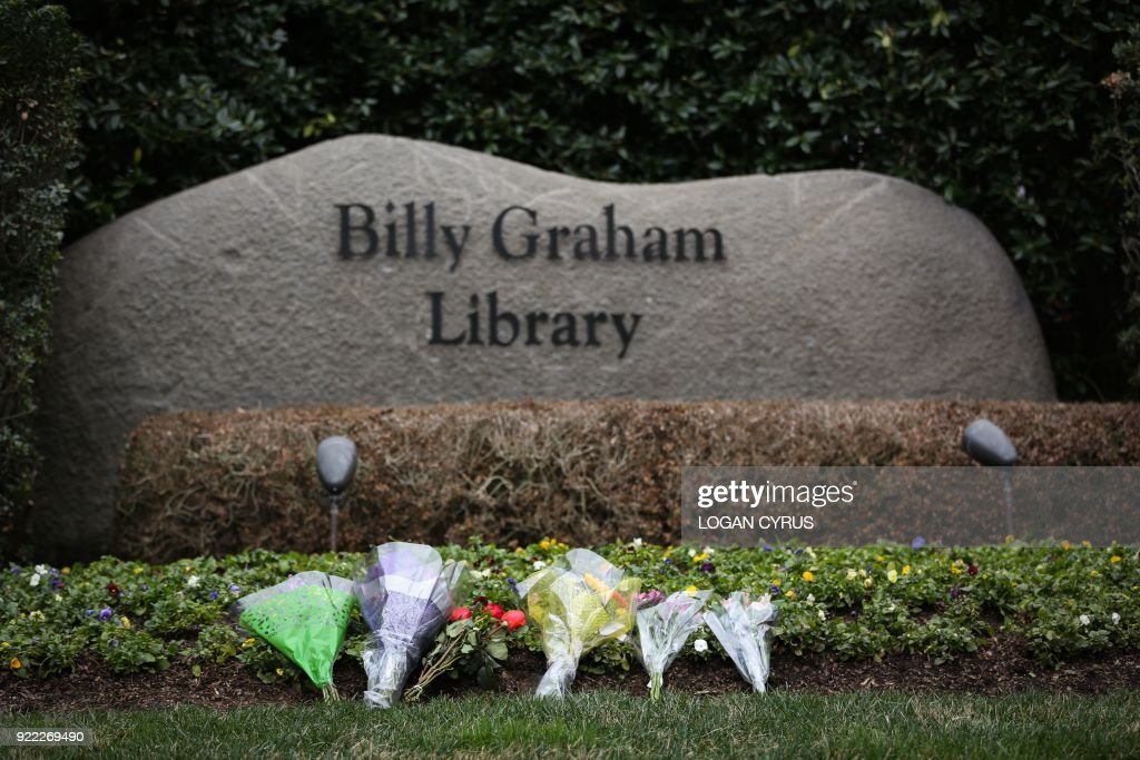 Flowers are left by mourners at the Billy Graham Library in Charlotte, North Carolina to pay respects hours after the announcement that Rev. Graham passed away in his home in Montreat, NC February 21, 2018. US presidents from Jimmy Carter to Donald Trump led the chorus of tributes Wednesday to the influential evangelist Billy Graham, a spiritual advisor to a dozen American leaders who has died at age 99. / AFP PHOTO / Logan Cyrus for AFP / Logan Cyrus