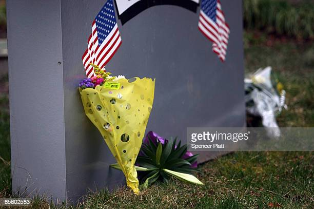 Flowers are left in memory of the victims in front of the American Civic Association where a gunman killed 13 people yesterday April 4, 2009 in...