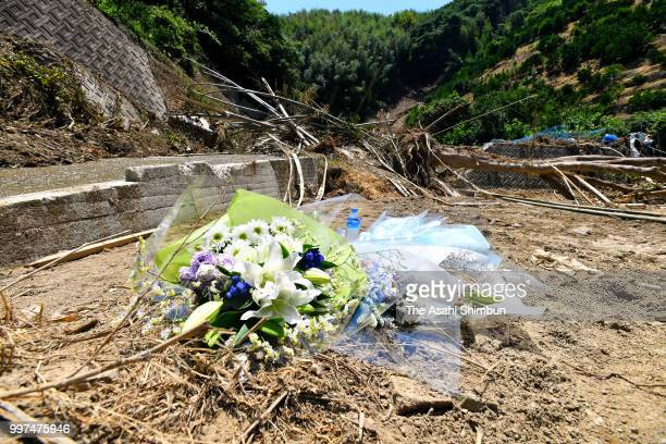Flowers are offered at a landslide site where three people were killed on July 13 2018 in Uwajima Ehime Japan The death toll from the torrential rain...