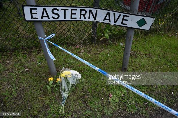 Flowers are pictured by a road sign on Eastern Avenue at Waterglade Industrial Park in Grays east of London on October 23 after the discovery of a...