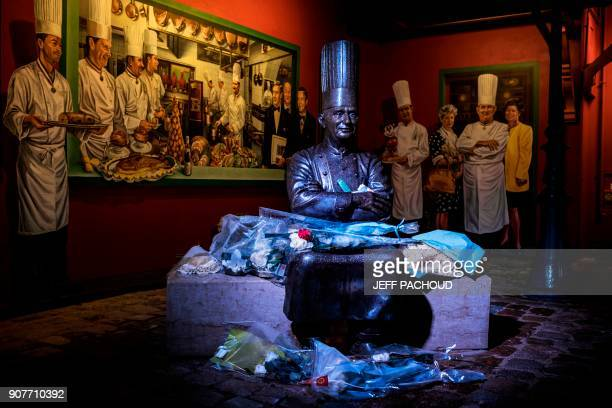 TOPSHOT Flowers are pictured next to a statue of French chef Paul Bocuse in the courtyard of his restaurant 'L'auberge du Pont de Collonges' on...