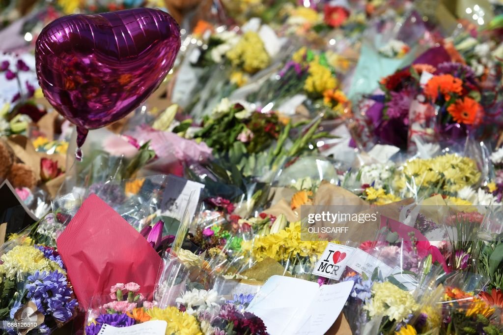 Flowers are pictured St Ann's Square in Manchester, northwest England on May 25, 2017, placed in tribute to the victims of the May 22 terror attack at the Manchester Arena. Police said they arrested two men Thursday in the Manchester area in connection with the deadly bombing of an Ariana Grande pop concert, while a detained woman was released without charges. Britain has raised its terror alert to the maximum level and ordered troops to protect strategic sites after 22 people were killed in a suicide bomb attack on a Manchester pop concert. / AFP PHOTO / Oli SCARFF