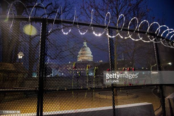 Flowers are placed along the razor wire fencing that now surrounds the US Capitol on January 15, 2021 in Washington, DC. After last week's Capitol...
