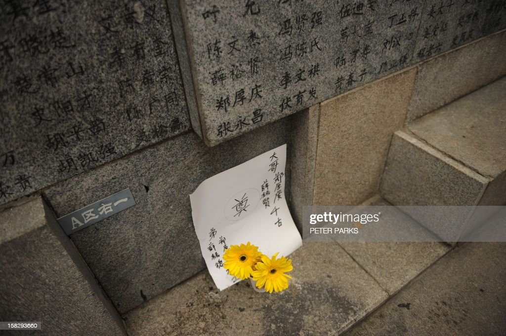 Flowers are placed at the base of a wall listing the names of victims to mark the 75th anniversary of the Nanjing massacre at the Memorial Museum in Nanjing on December 13, 2012. Air raid sirens sounded in the Chinese city of Nanjing on December 13 as it marked the 75th anniversary of the mass killing and rape committed there by Japanese soldiers -- with the Asian powers' ties at a deep low. AFP PHOTO/Peter PARKS / AFP PHOTO / Peter PARKS