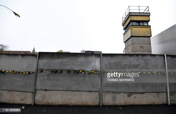 Flowers are placed at the Berlin Wall Memorial during the central commemoration ceremony for the 30th anniversary of the fall of the Berlin Wall, on...
