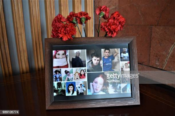 Flowers are placed behind pictures of the victims inside the Russian Embassy in Ankara Turkey on March 28 2018 during a commemoration for the victims...