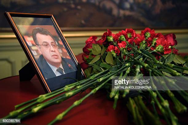 Flowers are placed in front of a portrait of Russian Ambassador to Turkey Andrei Karlov in the Foreign Ministry in Moscow on December 20 a day after...