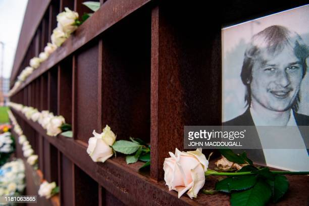 Flowers are placed in front of portraits of people who died trying to cross into west Berlin, at the Berlin Wall memorial, after official guests...