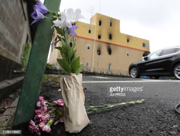 Flowers are placed near the Kyoto Animation company studio whiich set fire killing at least two dozen people in Kyoto on July 19 2019 A suspected...