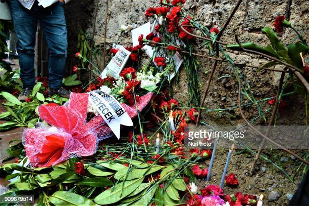 Flowers are placed next to the wall of a monument as people gather on the spot where Turkish journalist Ugur Mumcu was assassinated during a...
