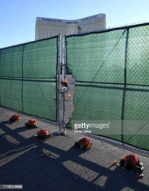 Flowers are placed on and next to a fence outside the Las Vegas Village across from Mandalay Bay Resort and Casino as a tribute to those killed...