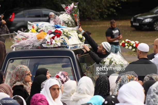 Flowers are placed on top of the hearses during a memorial prayer in Summerfield Park for three men killed during the riots earlier this month which...