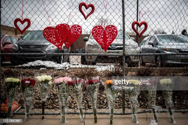 Flowers are seen at a fence outside the location where a gunman opened fire at a King Sooper's grocery store on Monday on March 23, 2021 in Boulder,...