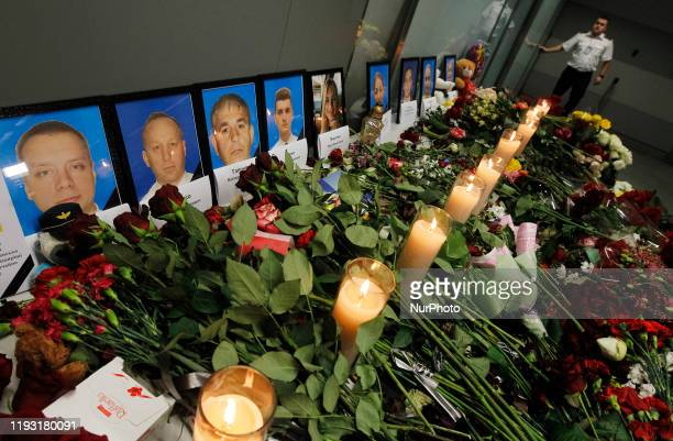 Flowers are seen near portraits of passengers and the crew members of the Ukrainian Boeing 737-800 plane, that crashed in Iran, at the Boryspil...
