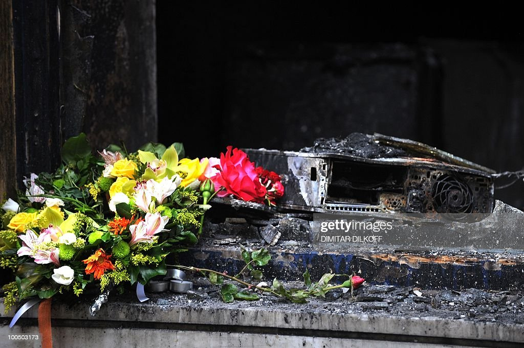 Flowers are seen on May 6, 2010 in front a branch of the Marfin bank where three people were killed in Athens. A fire-bomb attack on a bank in Greece killed at least three people on May 5, as police fought pitched battles with striking protestors furious at brutal budget cuts designed to avert national bankruptcy. Greek unions mobilised Thursday for new demonstrations against draconian austerity cuts as the government raced to push the unprecedented measures through parliament a day after deadly rioting.