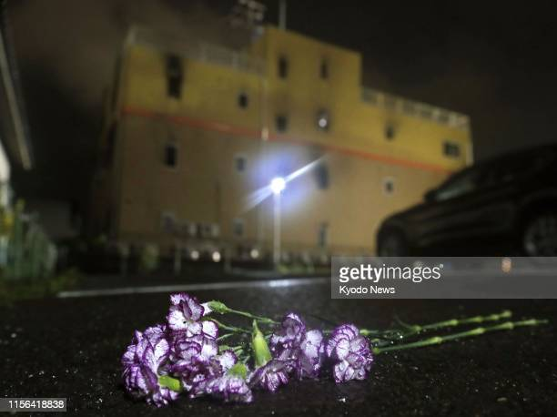 Flowers are seen placed on July 18 across the street from the threestory studio of Kyoto Animation Co in Kyoto which was set on fire by a man earlier...