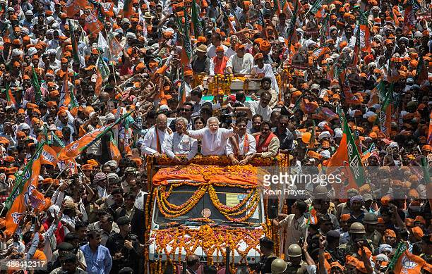 Flowers are thrown as BJP leader Narendra Modi waves to supporters as he rides on an open truck on his way to filing his nomination papers on April...