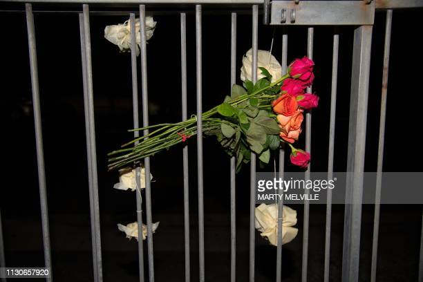 Flowers are tied to the fence on the front of the Wellington Masjid mosque in Kilbirnie in Wellington on March 15 after a shooting incident at two...