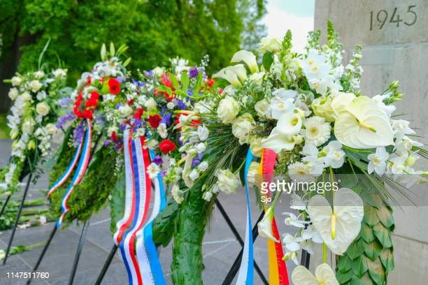flowers at a war memorial site after remembrance day in the netherlands - memorial event stock pictures, royalty-free photos & images