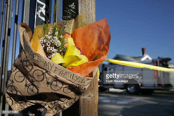 Flowers bearing the message 'you are my family' are placed near the scene following an overnight fire that claimed the lives of at least nine people...