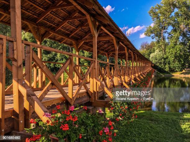 flowers blooming on covered bridge over river - covered bridge stock photos and pictures