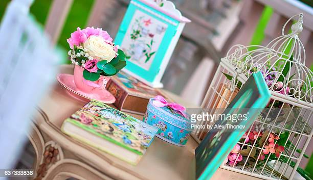 Flowers, book and birdcage on a table