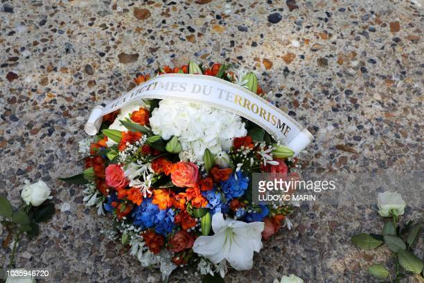 A flowers bouquet reading for the victims of terrorism lays in front of a memorial fountain during a national ceremony to pay tribute to the victims...