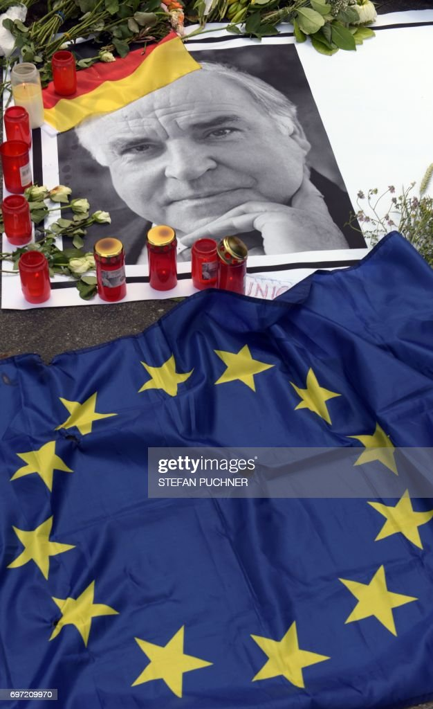 Flowers, candles and a flag of the European Union are placed on a picture of former German Chancellor Helmut Kohl in front of his house in Oggersheim near Ludwigshafen, western Germany, on June 18, 2017, two days after Kohl died. Helmut Kohl, the former German chancellor who seized the chance to reunite his country after years of Cold War separation, died at the age of 87 on June 16, 2017. / AFP PHOTO / DPA / Stefan Puchner / Germany OUT
