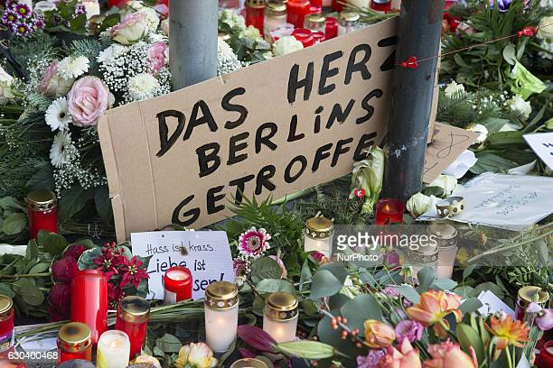 Flowers candles and a message reading 'the heart of Berlin hit' lay on the ground in a makeshift memorial close to the KaiserWilhelmGedaechtniskirche...