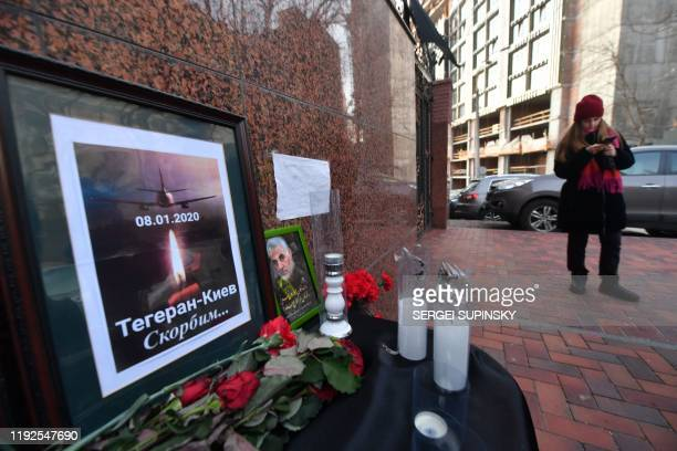 Flowers candles and a placard reading TehranKiev We mourn are seen placed outside the Iranian embassy in Kiev on January 8 in remembrance of the...
