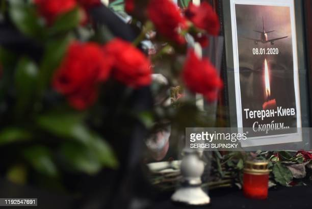 """Flowers, candles and a placard reading """"Tehran-Kiev We mourn"""" are seen placed outside the Iranian embassy in Kiev on January 8 in remembrance of the..."""