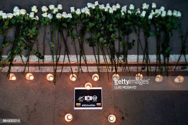 Flowers candles and a sign reading Not one more are seen during the funeral of Ecuadorean El Comercio journalist Javier Ortega photographer Paul...